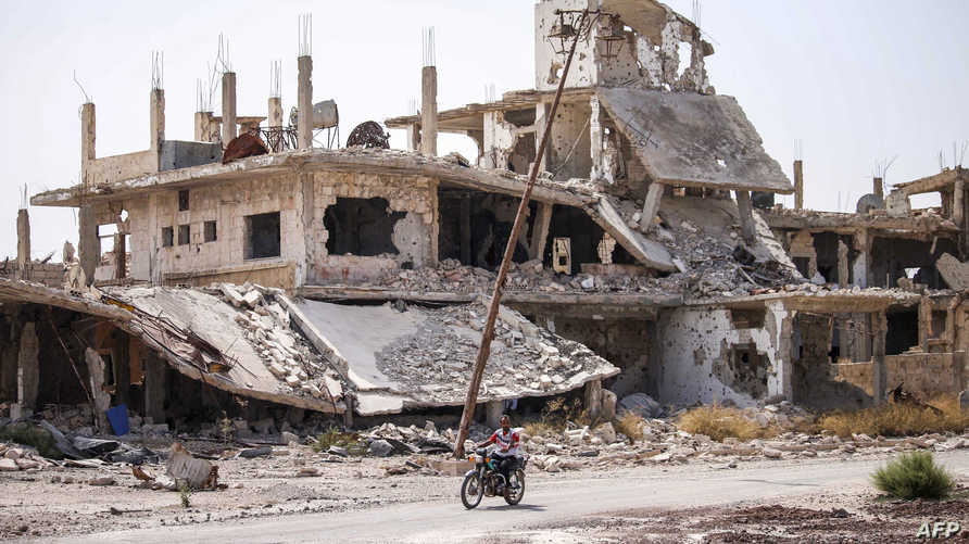 A Syrian rides a motorcycle past destroyed buildings in an opposition-held neighbourhood of the southern city of Daraa on…