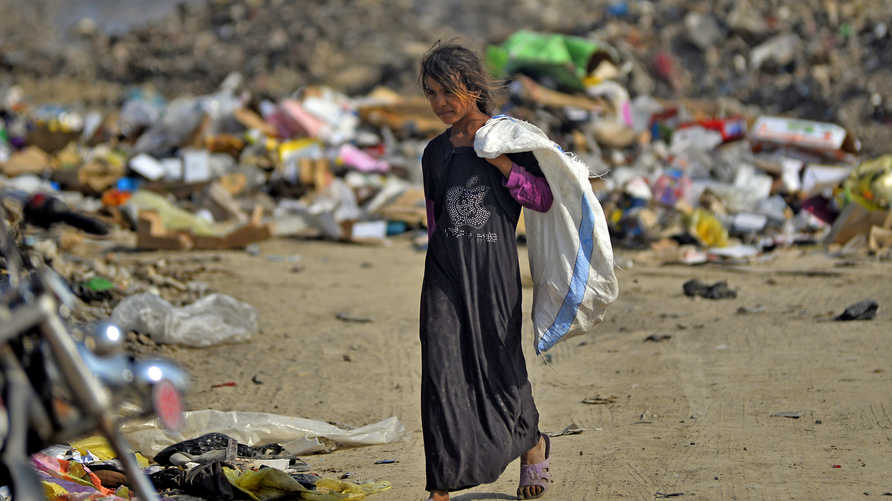 An Iraqi girl carrying a bag walks amidst piles of rubbish in a landfill in Diwaniyah, around 160 kilometres (100 miles) south…