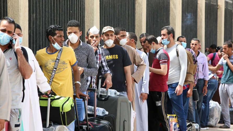 عمال مصريون أمام مدرسة في العاصمة الكويتية حولت إلى مركز إيواء بانتظار عودتهم إلى بلادهم