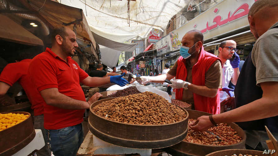 People buy dried fruits and nuts at a market ahead of the Muslim holy month of Ramadan, during the novel coronavirus pandemic…