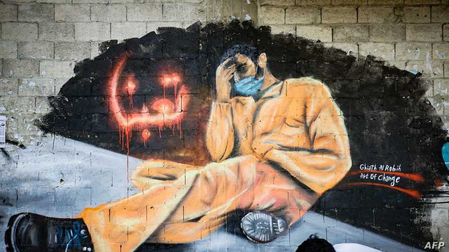 """A youth, wearing a protective mask, walks past a mural reading """"We are tired"""" in the Lebanese northern city of Tripoli on April…"""