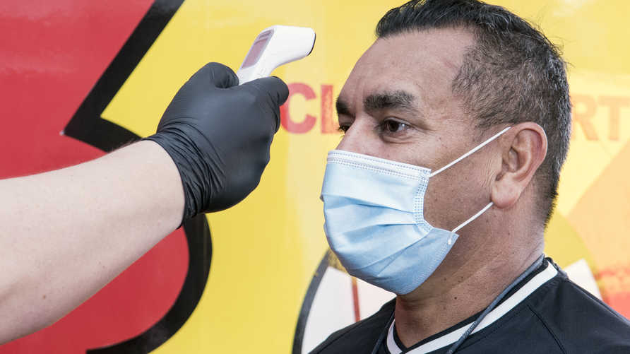 An employee checks the body temperature of Costa Rica's Sport Herediano coach Argentine Jose Giacone, before a training session…