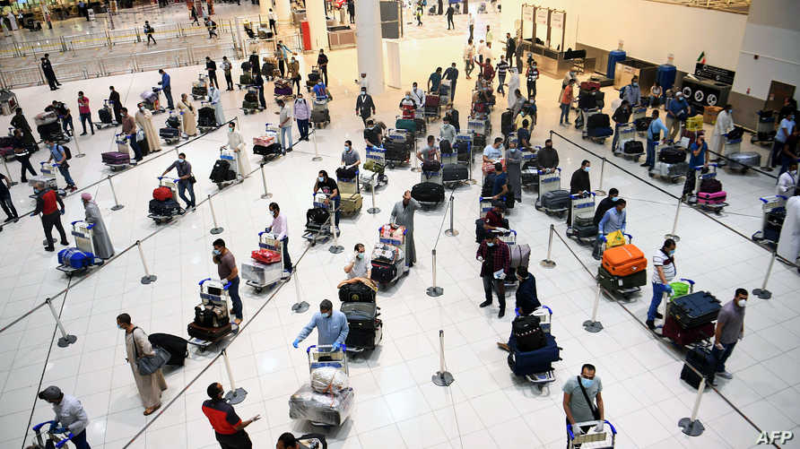 Egyptian citizens queue at Kuwait International Airport before boarding a repatriation flight to Cairo, in Kuwait City on May 5…