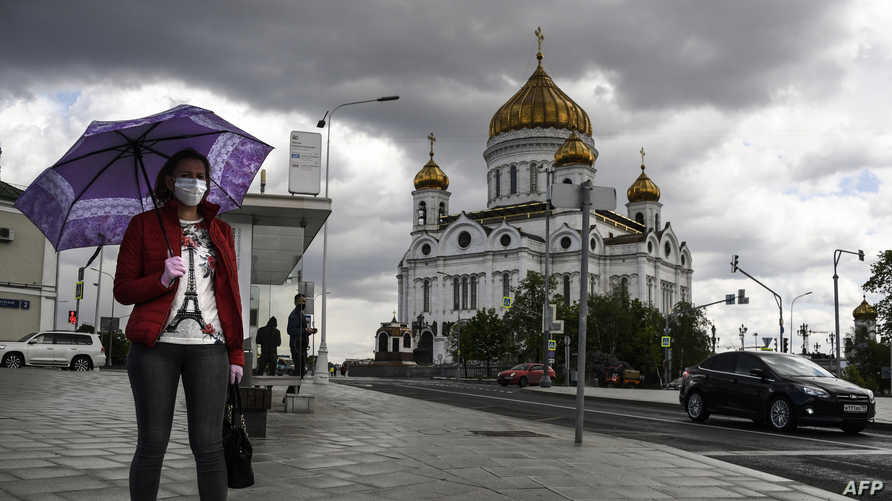 A woman walks past Christ the Savior cathedral in central Moscow on May 14, 2020, amid the outbreak of COVID-19, caused by the…