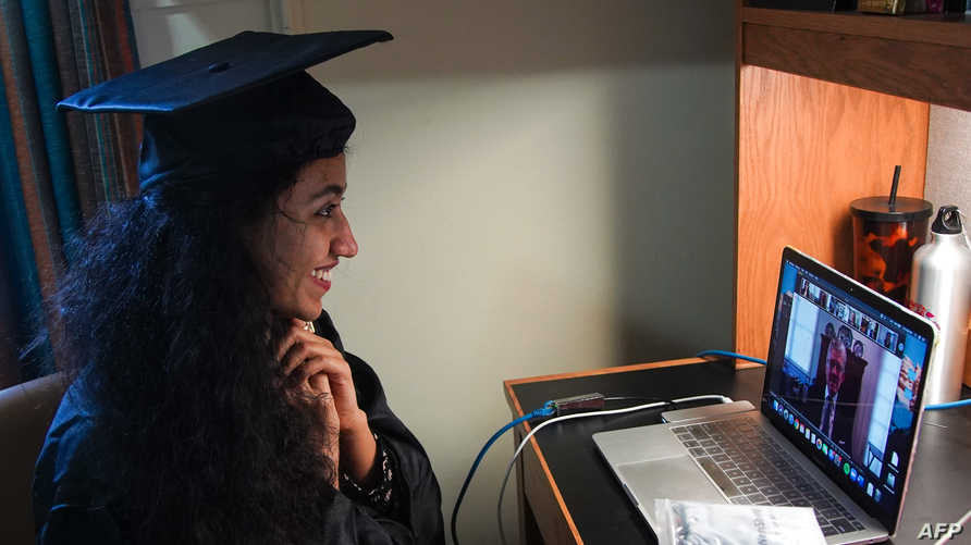 Pakistani student Varsha Thebo, 27, attends her online graduation ceremony in her bedroom at the International Student House…