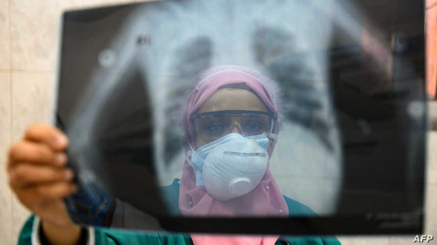 (FILES) In this file photo taken on April 19, 2020, an Egyptian doctor wearing two protective masks checks a patient's lung X…