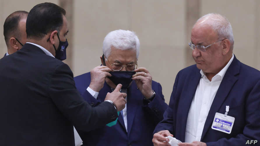 Palestinian President Mahmoud Abbas wears a protective mask after charing the Palestinian leadership meeting at his…