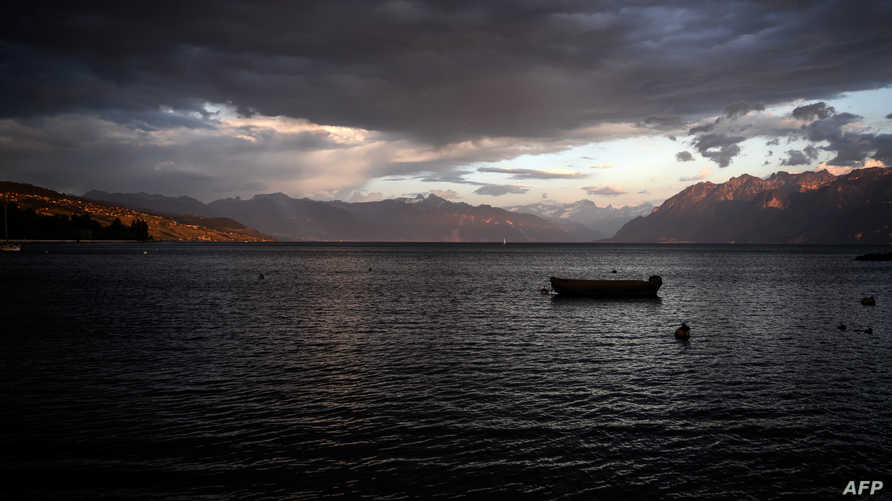 A picture taken on May 19, 2020 shows a small boat under dark clouds at sunset on the shores of Lake Geneva in Lausanne. (Photo…