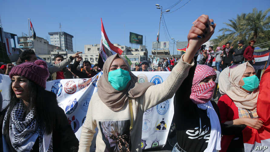 (FILES) In this file photo taken on February 4, 2020, Iraqi students hold hands and chant as they march in an anti-government…