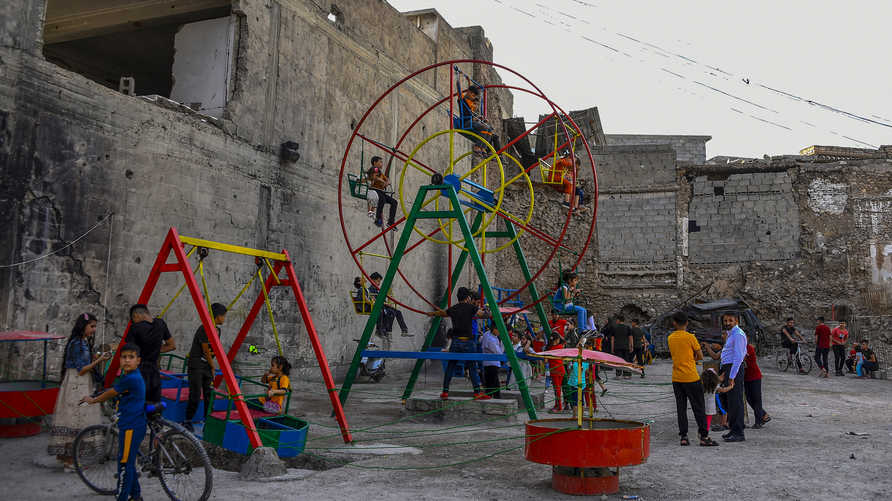 Iraqi children play at a playground during celebrations of the Eid al-Fitr feast marking the end of the Muslim holy month of…