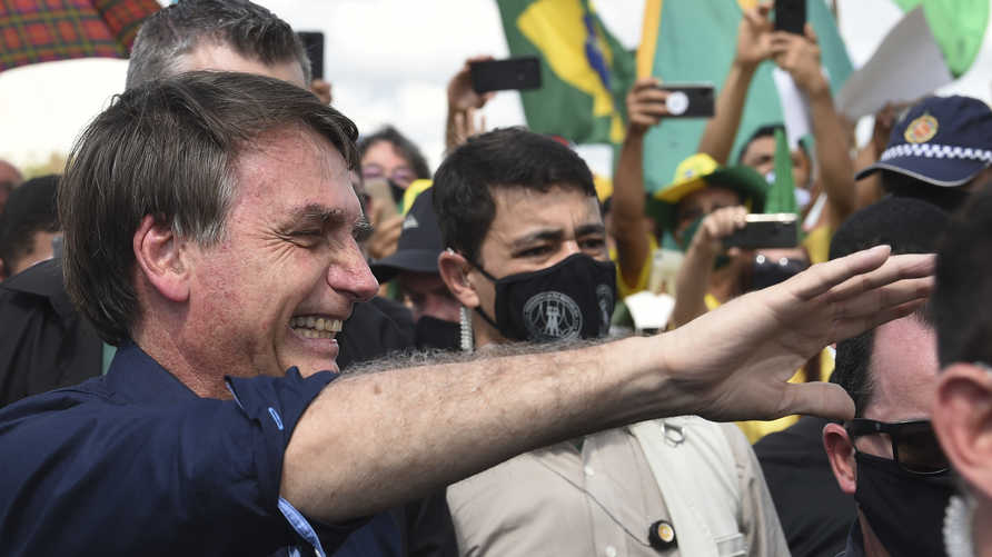 Brazil's President Jair Bolsonaro greets supporters upon arrival at Planalto Palace in Brasilia, on May 24, 2020, amid the…