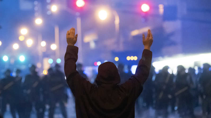 A protester faces off with police during rioting and protests in Atlanta on May 29, 2020. - The death of George Floyd on May 25…