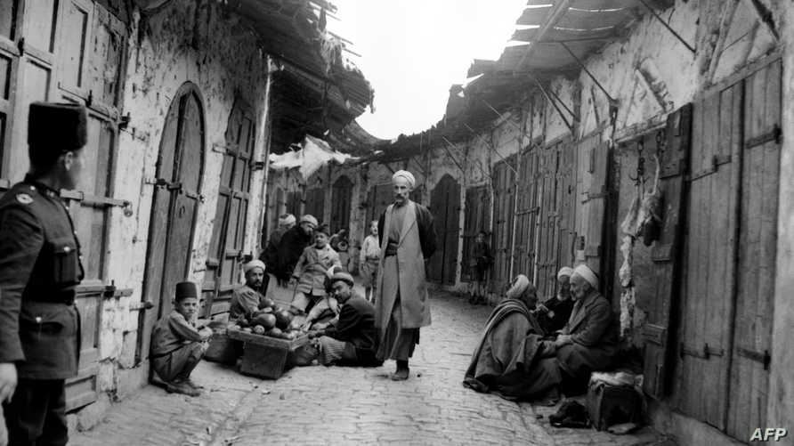 A picture released 27 October 1938 during the British Mandate in Palestine shows Palestinian Arabs watched by a policeman in a…