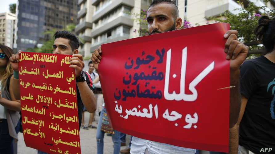 "A Lebanese protester (R) holds a placard reading in Arabic ""Refugees, residents, all of us against racism"" on July 18, 2016 in…"