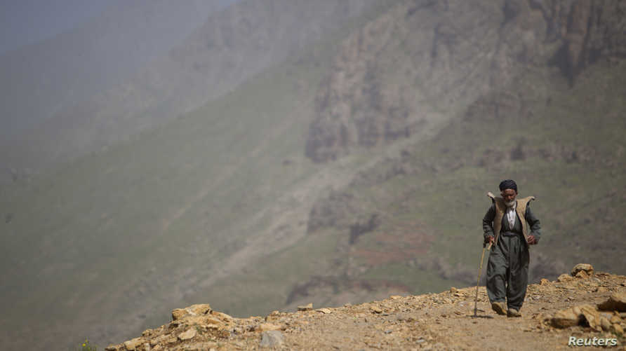 An Iranian Sunni Kurd walks along a mountain in Ouraman Takht village in Kurdistan province, about 620 km (385 miles) west of…
