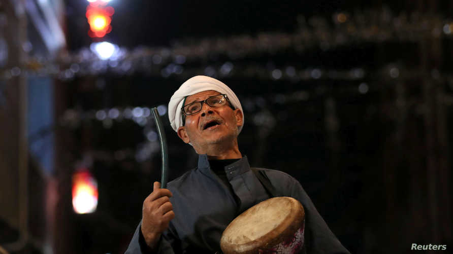 Al-Masharty Moustafa, 60, beats a drum as he wakes residents to eat their pre-dawn Suhoor meals before beginning their fasting…