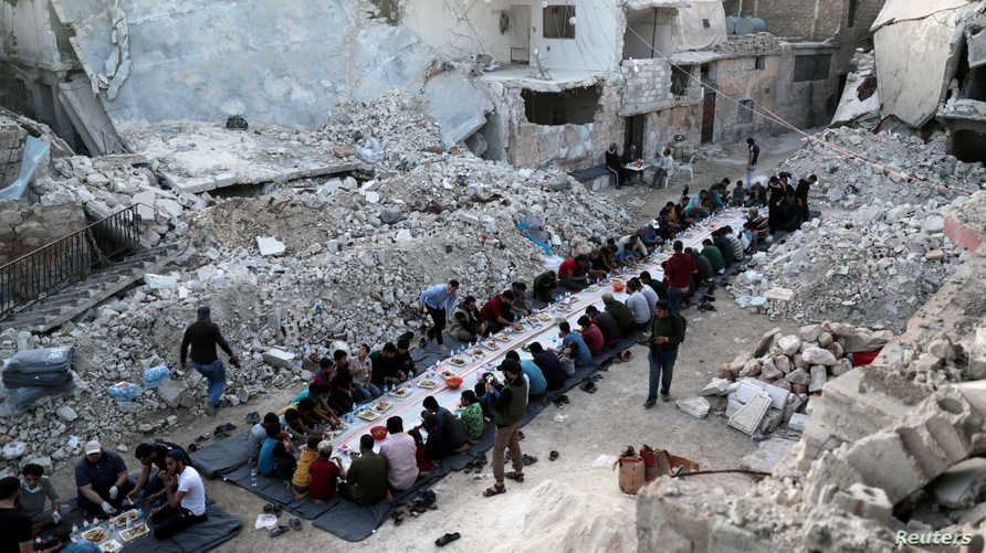 People eat their Iftar meal provided by a group of volunteers in a damaged neighbourhood, amid fear for the coronavirus disease…