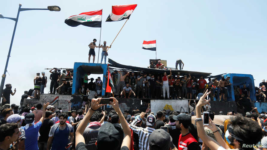 Demonstrators gesture as they take part in the ongoing anti-government protests after newly-appointed Iraqi Prime Minister…