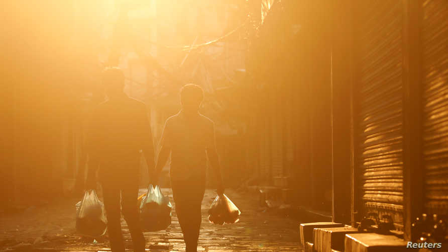 Men carrying relief walk along a deserted street as the sun sets during the fifty-two day of the lockdown imposed by the…