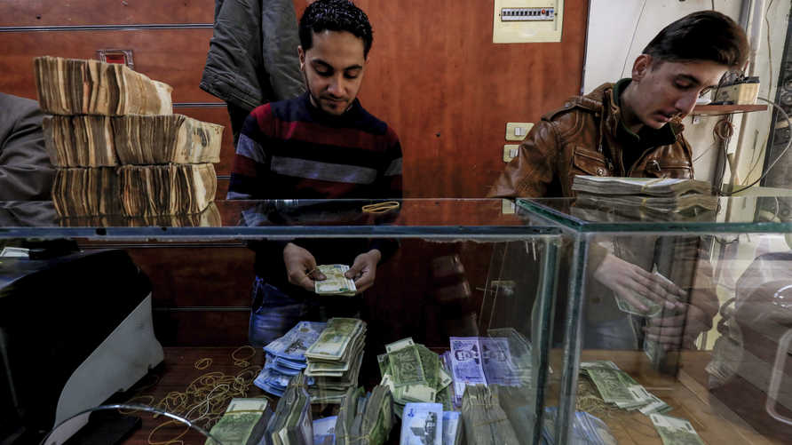 Employees of a currency exchange counter count banknotes at  market street in the northeastern Syrian town of Qamishli on May 2…