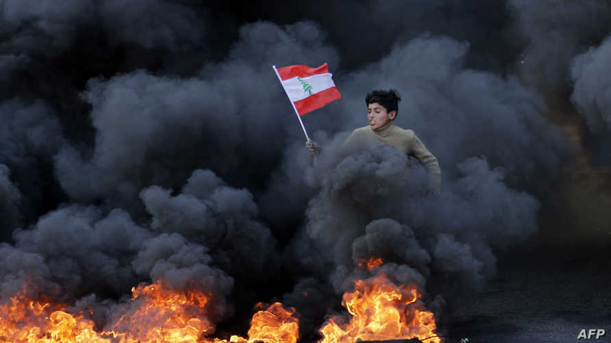 A Lebanese youth runs with a national flag as smoke billows from burning tires during a demonstration in Jal el-Dib area on the…