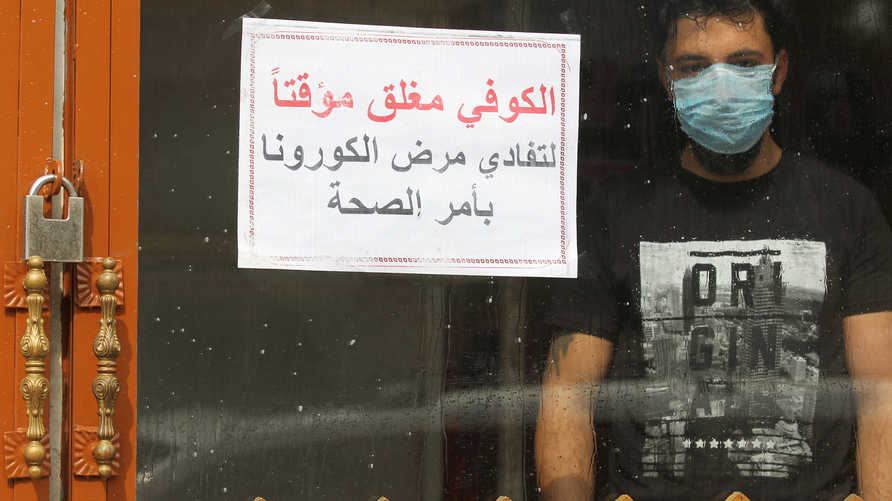 "An Iraqi man, wearing a protective mask, stands inside a coffee shop with a sign in Arabic which reads ""Coffee shop is closed,…"