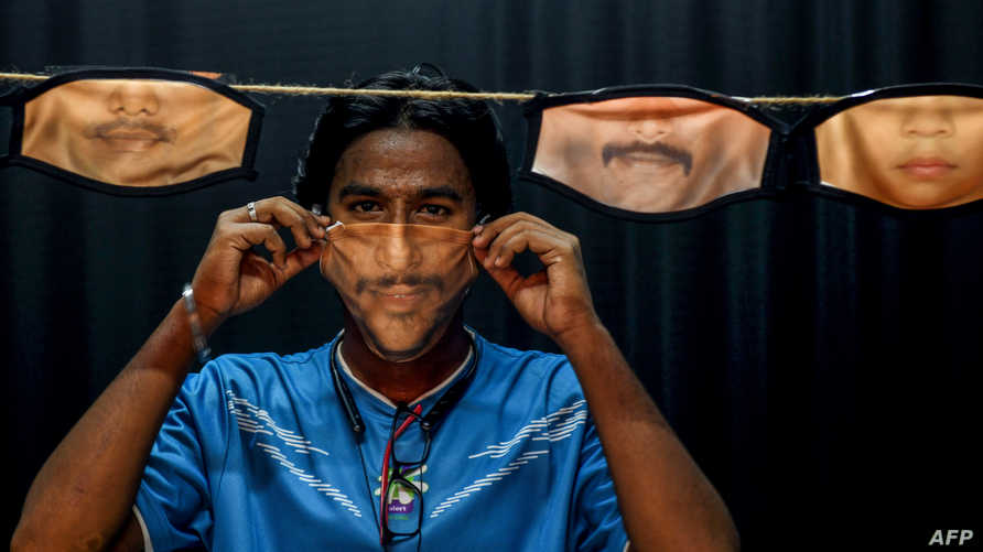 A man adjusts a facemask with his face's image printed on it created at a photo studio as other facemasks are hung amid…
