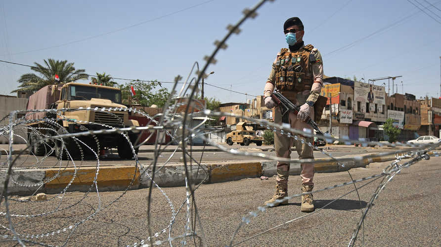 A member of the Iraqi security forces stands guard at a checkpoint, enforcing a curfew due to the COVID-19 coronavirus pandemic…