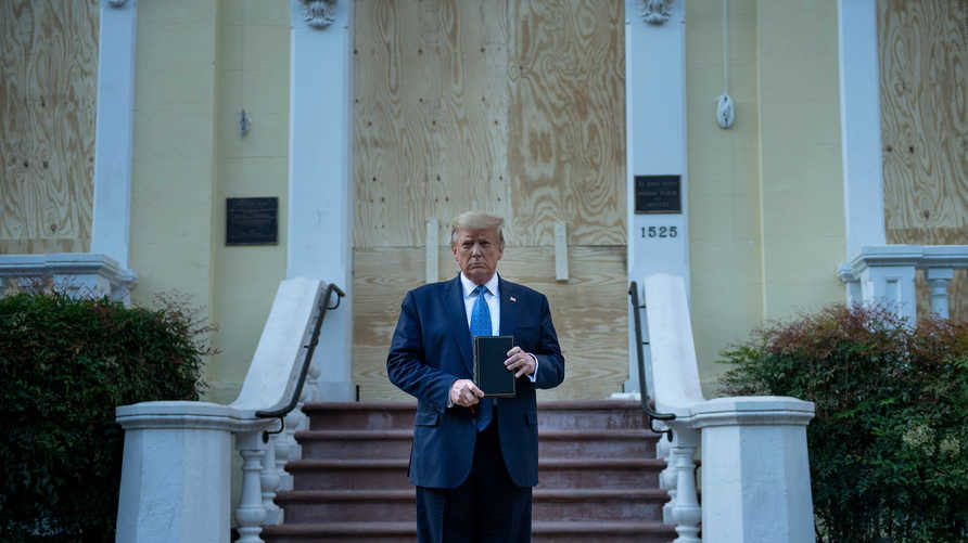 US President Donald Trump holds a Bible while visiting St. John's Church across from the White House after the area was cleared…