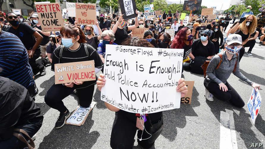 متظاهرون يقومون بحركة ركوع الركبة الواحدة تعبيرا عن سلمية احتجاجهم