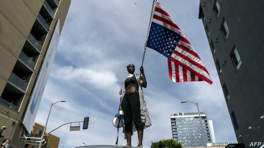 A protesters takes a moment while speaking to the crowd as they march through Hollywood during a demonstration over the death…