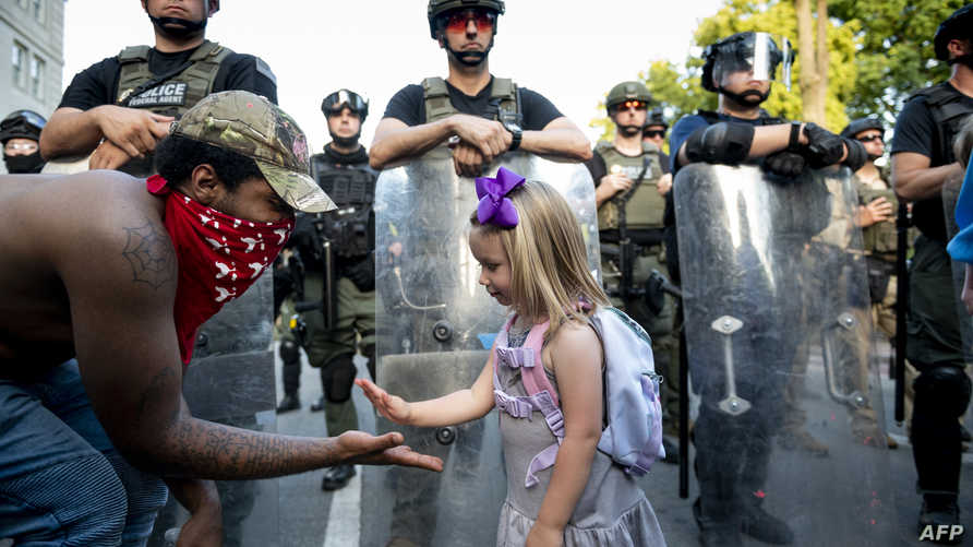 Twenty-nine-year old DC resident, George (L), slaps hands with three-year-old Mikaela (R) in front of a police barricade on a…