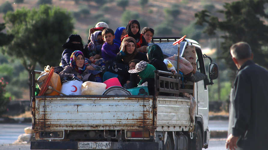 Displaced Syrians sit in the back of a truck loaded with belongings as they flee along the M4 highway, in Ariha in the rebel…