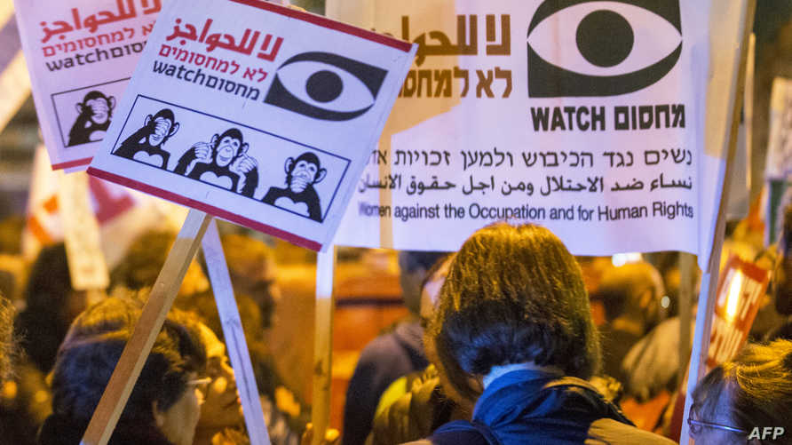Israeli left-wing activists hold placards during a 'Peace Now' march calling on Israelis to choose ''another way'' and end the…
