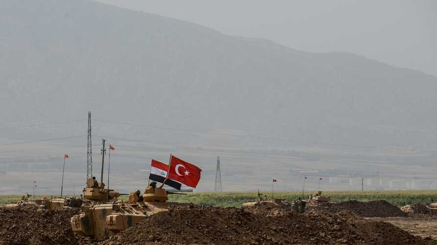Soldiers stand on tanks bearing Turkish and Iraqi flags during a joint military exercise near the Turkish-Iraqi border at…