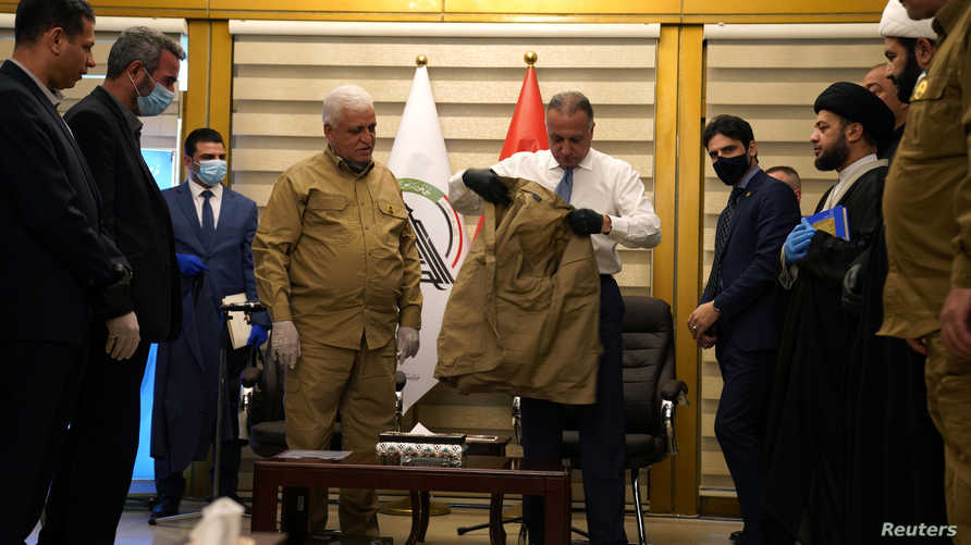 Iraqi Prime Minister Mustafa al-Kadhimi wears a military uniform of Popular Mobilization forces during his meeting with Head of…
