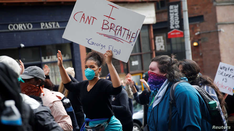 "A woman holds up her hands as she carries an ""I can't breathe"" sign during protest against the death in Minneapolis police…"