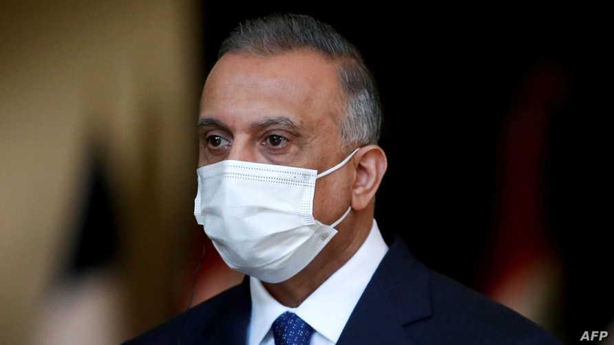 Iraq's Prime Minister Mustafa al-Kadhemi, mask-clad due to the COVID-19 coronavirus pandemic, looks on during a joint press…