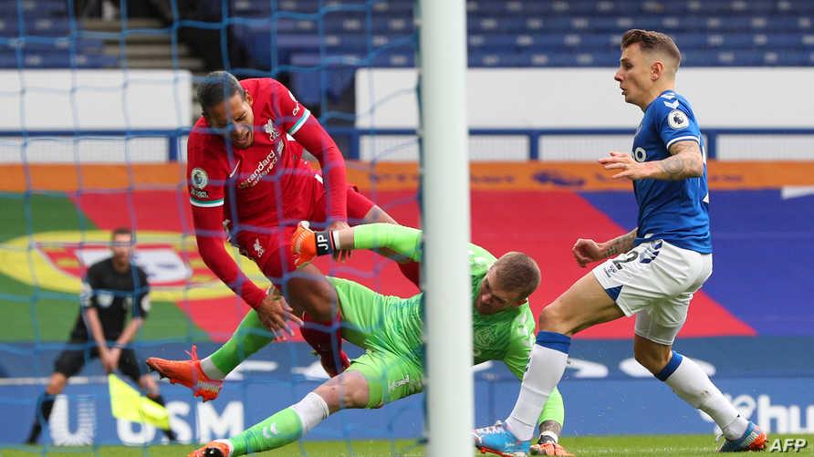 Everton's English goalkeeper Jordan Pickford (C) tackles Liverpool's Dutch defender Virgil van Dijk (L) during the English…