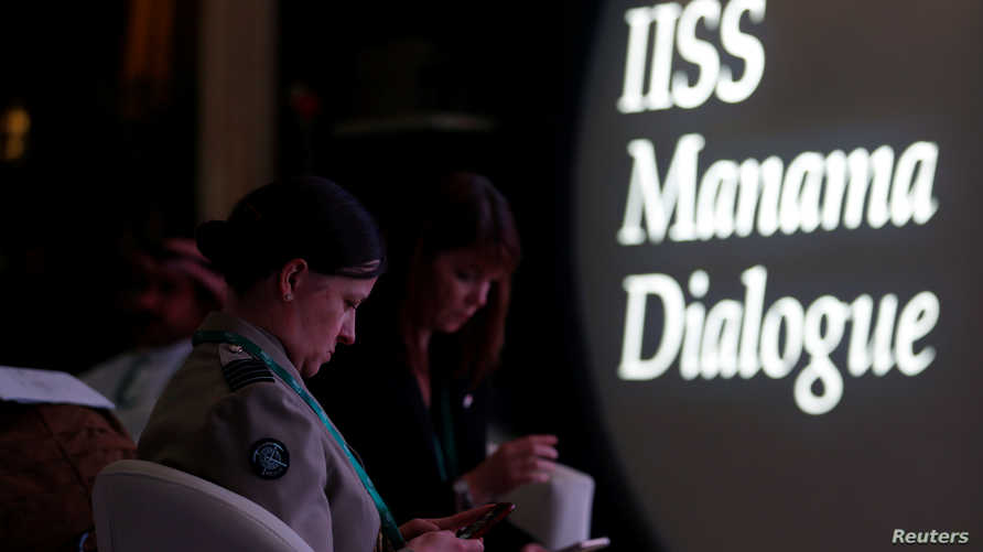 German military officials check their mobile phones during the 15th Regional Security Summit IISS Manama Dialogue 2019, in…