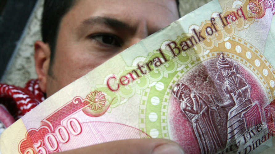 An Iraqi man checks the authenticity of a 25,000-dinar bill before using it in a shop in central Baghdad, 29 January 2008. It…