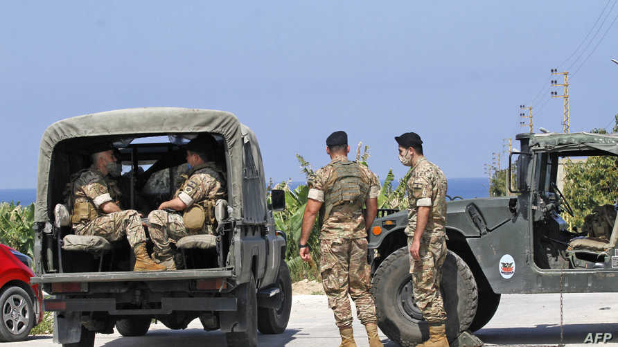 Lebanese soldiers stand guard in the southern Lebanese town of Qlaile on May 14, 2021. - Three rockets were fired from southern…