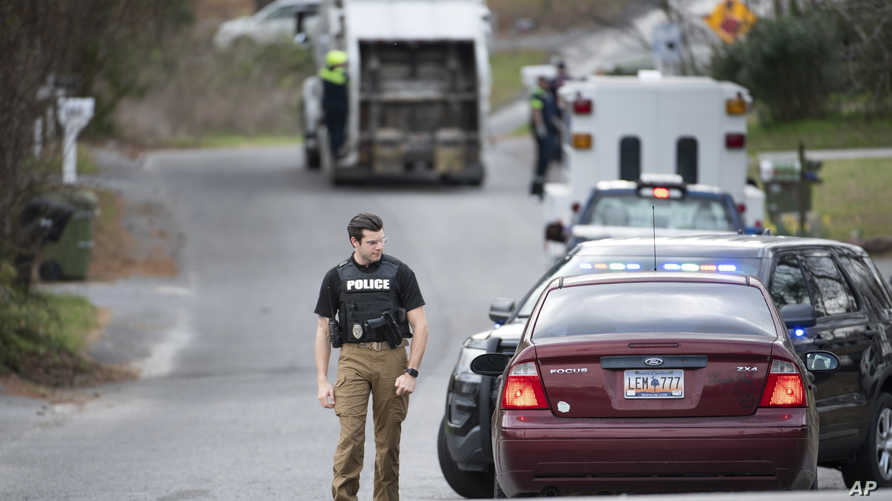 A Cayce police officer approaches a vehicle at a road block near an entrance to the Churchill Heights neighborhood Thursday,…