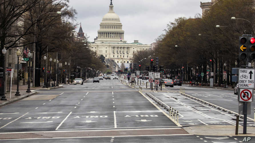 With the U.S. Capitol building in the background, motorists drive on Pennsylvania Avenue NW, Wednesday, March 25, 2020, in…
