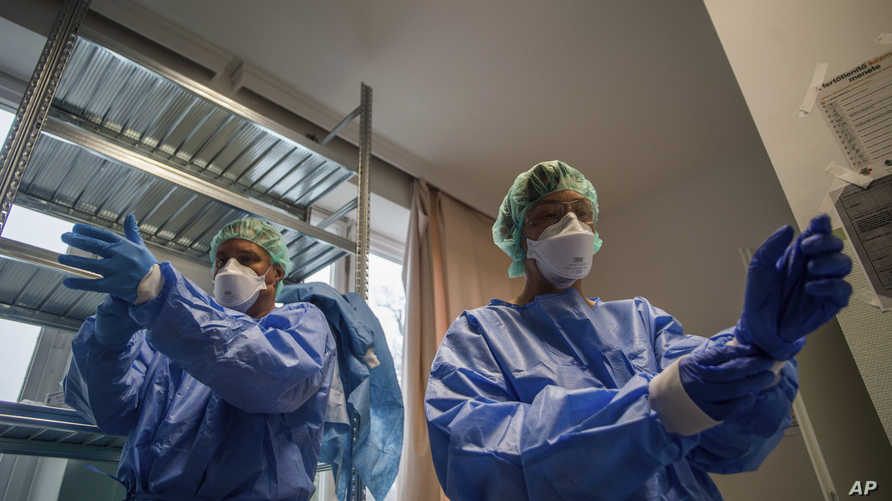 Doctors take on protective suits before they enter the isolation room at the care unit of the new COVID-19infected patients…