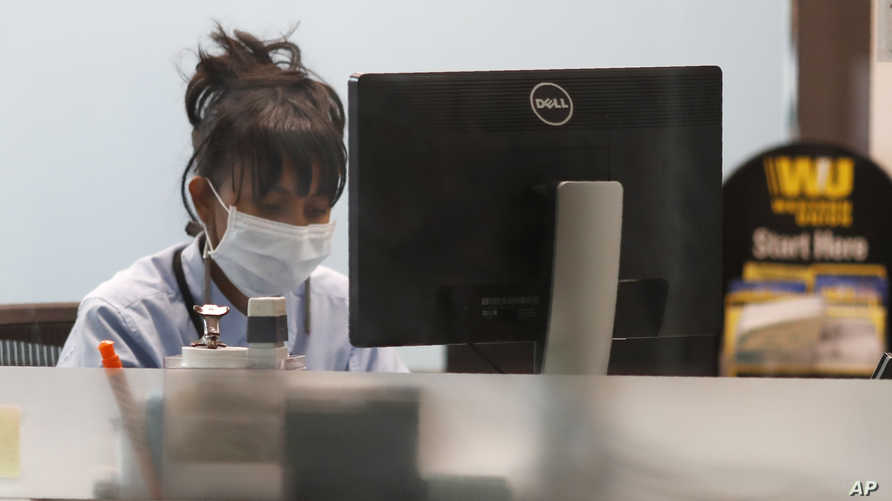 A currency exchange worker wears a mask as she works on a computer in her kiosk in Denver International Airport as travelers…