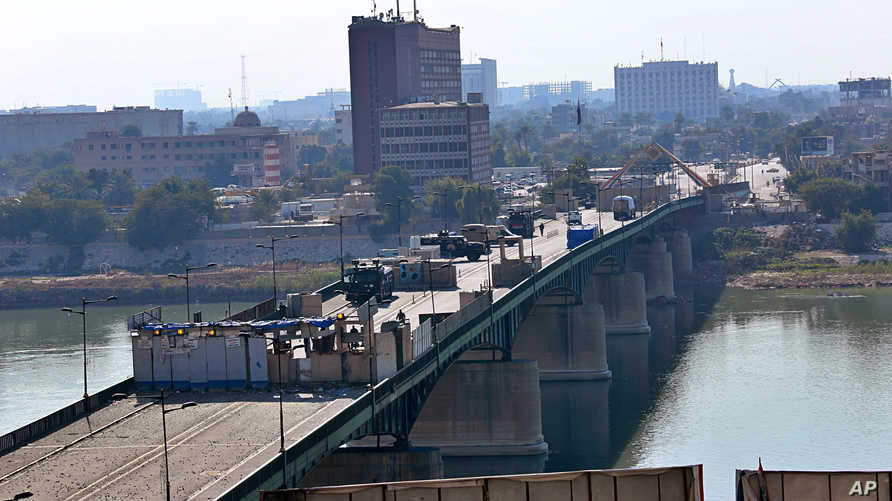 Security forces close a bridge leading to the Green Zone government areas, during ongoing anti-government protests in Baghdad,…