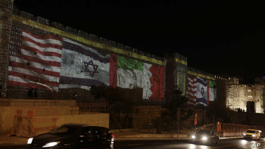 Representations of the U.S., Israeli, Emirati and Bahraini flags are projected onto a wall of Jerusalem's Old City, marking the…