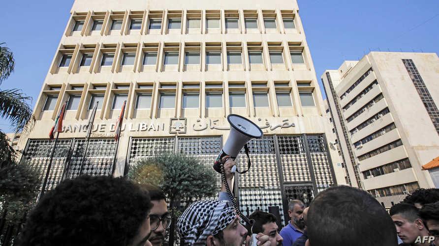 مظاهرة أمام مصرف لبنان المركزي في طرابلس في نوفمبر 2019. ,تحولت المصارف اللبنانية، خلال الأشهر الماضي، إلى ميدان إشكالات بين مواطنين يطالبون بأموالهم وموظفين ينفذون القيود المشددة