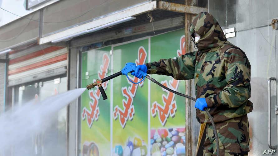 عنصر في الدفاع المدني العراقي يرش محاليل تعقيم
